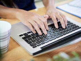 Frau, die am Laptop eine E-Mail schreibt