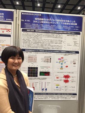 新井准教授、ポスターの前でパチリ。