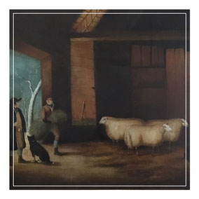 A farmer with his shepherd and prize sheep in a barn