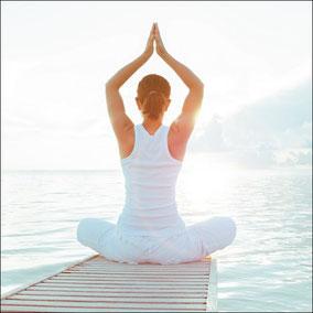 Frau macht Yoga auf Bootssteg am Wasser