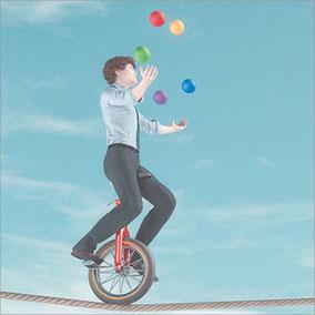 Junger Mann jongliert auf Einrad auf dem Seil