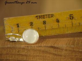 Der Ohrhänger liegt vor einem Zollstock der eine Länge von 24 mm anzeigt.