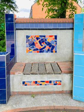 Linke Bank der dreiteiligen Sitzbank: Beton, Holz, Fliesen und farbige Keramikfliesen wurden zu einem Kunstobjekt zusammengefasst (Foto: 05-2020, Jens Schmidt)
