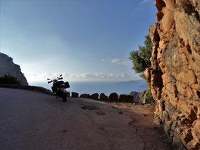 Motorradreisen Bild mit Strasse, Motorrad, Felsen und Blick aufs Meer
