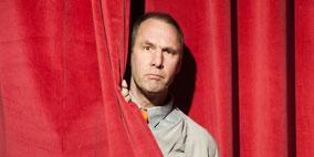In der Rolle von Professor Schlabotnik schaut Peter Schütte hinter dem Bühnenvorhang vor