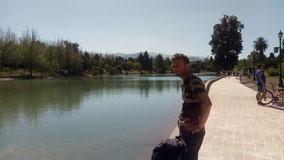 Jérôme devant le canal du parc San martin de Mendoza, sous le ciel bleu. Derrière quelques randonneurs et cyclistes.