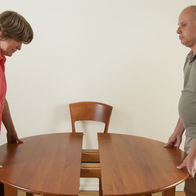 Woman and man push together a table by VisualsSpeak.