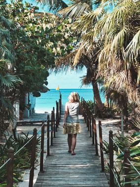 Frau läuft auf einem Holzsteg umringt von Palmen aufs Meer zu.
