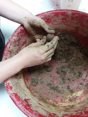 Zwei Hände formen über einer roten mit Erde und Lehm verkrusteten Schüssel eine Blumenkugel. Die Anleitung zur Herstellung von Seedboms findest Du hier. DIY, Blumenkugeln selber machen