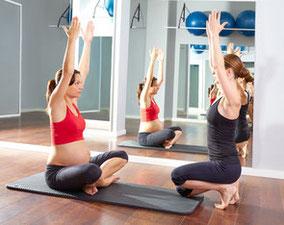 Schwangere Frau beim Training mit Pilates Coach