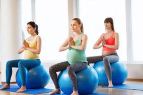Pilateskurs mit schwangeren Frauen auf Gymnastikball