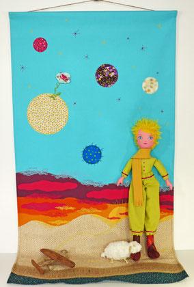 Le Petit Prince est une poupée de textile (hauteur 47cm) et son mouton de laine, sur sa toile de dunes (54 x 98cm), coucher de soleil et planètes, ainsi que l'avion en bois flotté, pièce unique
