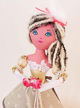 Gloria est une poupée décorative, composée de textiles et remplie de ouate, vêtue de cotonnades, dentelles, rubans et plume, maquillée à la peinture acrylique, taille 50 cm, pièce unique, disponible