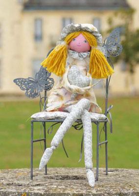 Agathe est une poupée décorative composée de textiles, elle enlace dans ses bras un cœur de coton assorti à son costume, elle tient assise sur tout support, taille 40 cm, pièce unique, disponible