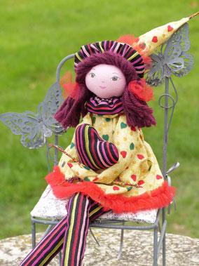 Magali est une poupée décorative composée de textiles, elle enlace dans ses bras un cœur de coton assorti à son costume, elle tient assise sur tout support, taille 40 cm, pièce unique, disponible