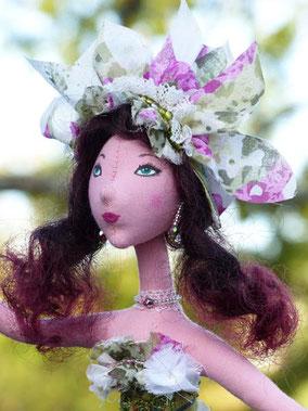 Ida est une poupée décorative, composée de textiles et remplie de ouate - Vêtue de cotonnades, dentelles, rubans, perles - Maquillée à la peinture acrylique - Elle se pose sur son tapis vert en laine bouillie - Taille 42 cm - Pièce unique - Disponible