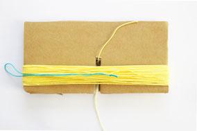 吊り糸になる糸を用意し玉結び(緑糸)。真ん中より右側に配置。段ボールの切り込みから15cmほどの糸を通し結びます。