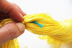 吊り糸を指で真ん中の方へ潜らせます