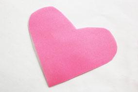 クリアファイルに折り紙を挟み、はさみでハート形に切る。横幅は10〜13cmがおすすめ