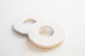 ペットボトルキャップとココットを型にしてドーナツ状に切り抜いたシチレンボードにふわふわ素材の毛糸をぐるぐる巻きつけ1週させる