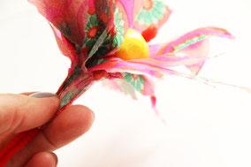 モールを持ち、ナプキンの柄がお花の中央を向くように包みこみます