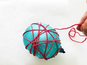 硬く絞って水風船に糸を巻きつけていきます