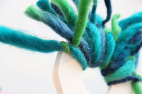 緑の人超は毛糸を15cm幅に切り結びつけていく。中央の穴にペットボトルのキャップをさし込んで完成