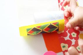 トイレットペーパーの芯の片方を折り紙の端に合わせて糊で貼り付ける