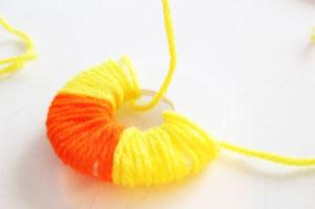 ドーナツ型のシチレンボードに毛糸を巻きつける