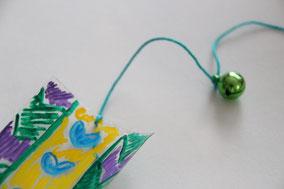 描き終わったら穴を開け紐を付け、鈴とダイヤを紐でつなぎ完成