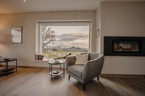 Wohnzimmer mit Sofa und Kamin, im Hintergrund schöne Aussicht