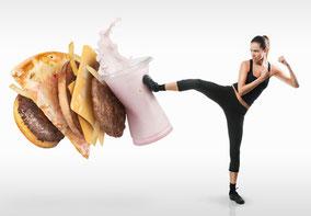 Junge Frau bekämpft Fast Food als Kickboxerin