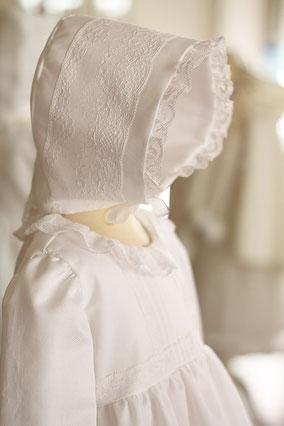 Bonnet baptême bébé en coton blanc et dentelle de Calais. Modèle béguin bébé Marie, Fil de Légende. Magasin vêtements baptême Paris, Neuilly-sur-Seine. Expédition en France et à l'international.
