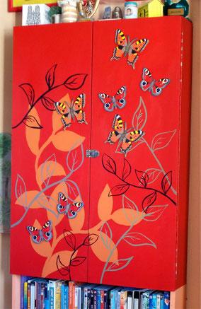 Peinture sur meuble : fond rouge avec feuillage, papillons en bois peints collés dessus.