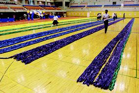 今回ギネス認定がされた「折り鶴ロープ」(左)と、認定を受け笑顔を見せる桑江市長、認定員のマクミラン舞氏=7日、沖縄市体育館
