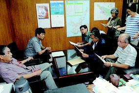 漢那副市長(左手前)が上原共同代表(右中央)に要請への回答文を手渡した=14日午後、市役所