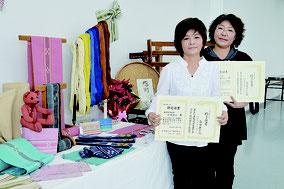 修了証を受け取った古謝さん(左)と古堅さん。講習中に織った品々も展示された=9日、みんさー工芸館
