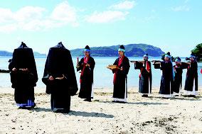 祖納集落では、黒頭巾をかぶったフダチミや女性たちによるアンガー行列が行われた=14日午後、西表島前泊海岸