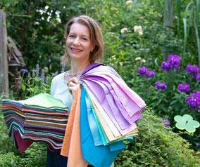 Vera Löwe steht vor einem Blumenbeet mit einem Stapel bunter Tücher auf dem Unterarm und über der Schulter weitere farbigeTücher.
