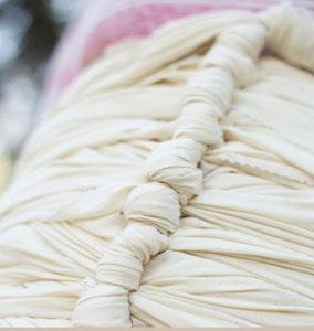 Nahaufnahme einer Frau, die den tradizionellen Benkung Schal trägt. Der Fokus ist hierbei auf die vielen Knoten, die hierbei benötigt werden.