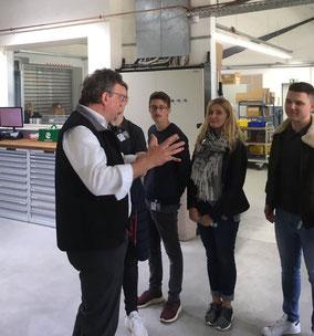 Ein Geschäftsführer steht mit einer Gruppe in einer Werkhalle.