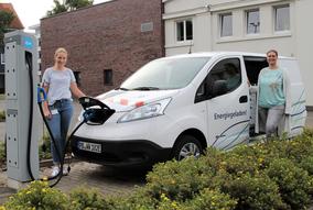 Foto (WWE): Leonie Riekschnitz von Westfalen Weser Netz und Maren Scheffler von der Klimaschutzagentur tanken den Kastenwagen.
