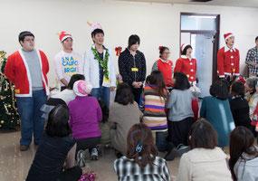 クリスマス会で出し物を披露する学生ボランティア