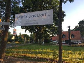 """Zwischen hohen Bäumen hängt ein Banner am Hüder Dorfplatz auf dem der Slogan steht """"Hüde. Das Dorf ... entdeckt uns hier www.huede.eu"""""""