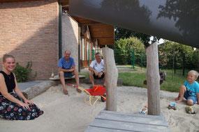 Am Rand des Krippen-Sandkastens sitzen die Krippenleiterin, die Segelspender Mathias Jakobtorweihen und Jens Dannhus und ein Junge im Schatten.