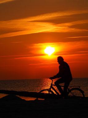 per Rad in den Sonnenuntergang Hiddensee