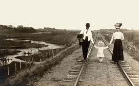 A late 19th century family taking a stroll down a set of railroad tracks