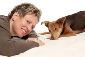 Hundetrainerin liegt mit Hund auf dem Boden