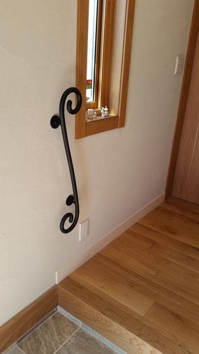 玄関に無垢材を使ったクッルッとスチール手すり