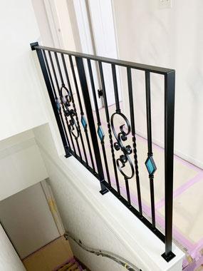 唐草デザインアイアン手すりとダイヤ型のオシャレで空色のステンドグラス